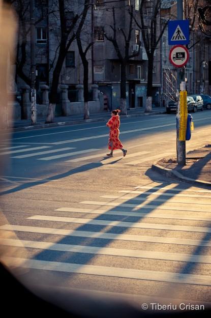 O femeie cu halat rosu pe trecerea de pietoni