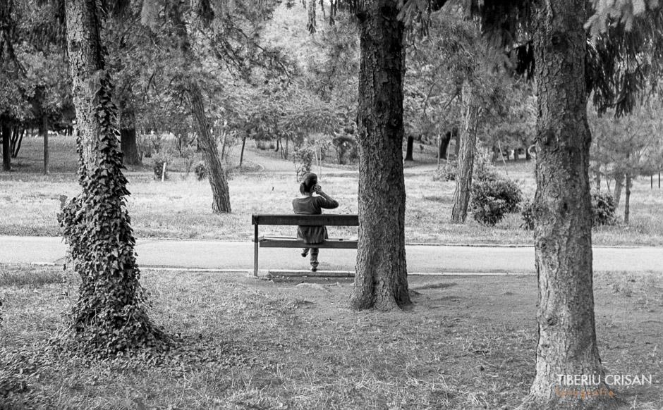 O femeie vorbeste la telefon pe o banca din parc